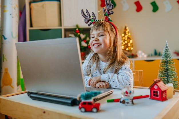 Девочка с помощью ноутбука для видеозвонка в детской комнате во время рождества