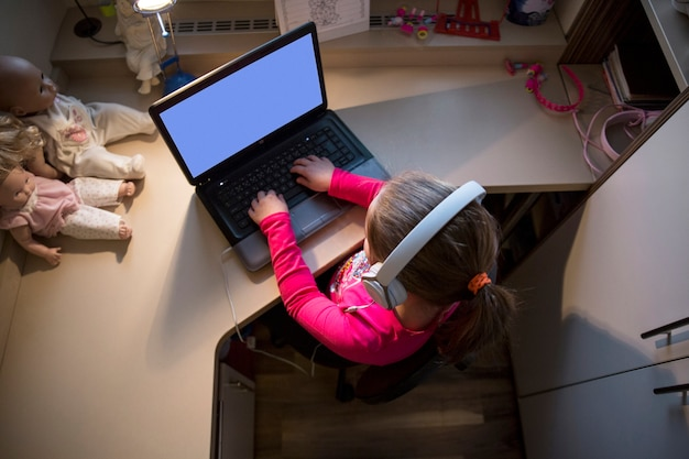 Girl using laptop in small room