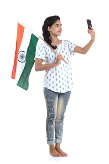 Girl using mobile with indian flag or tricolour on white wall, indian independence day, indian republic day