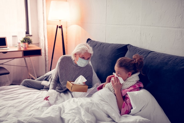 Girl using napkins. girl using napkins while having running nose near her caring granny wearing protective mask