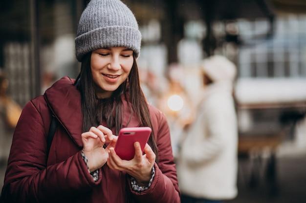 여자는 거리 밖에서 전화를 사용하고 친구들과 회의