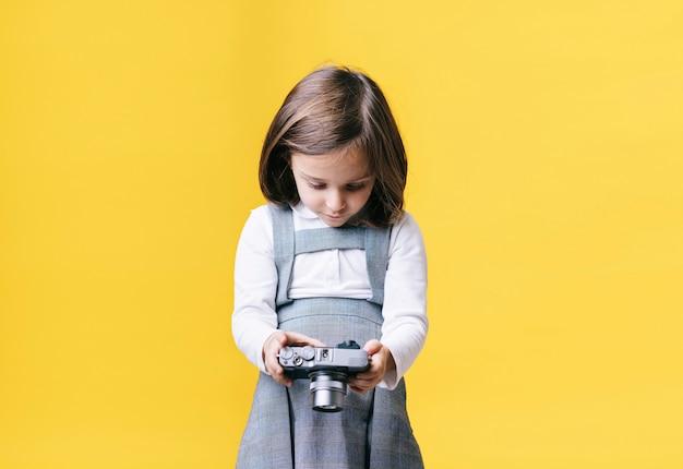 Girl using a photo camera on yellow wall