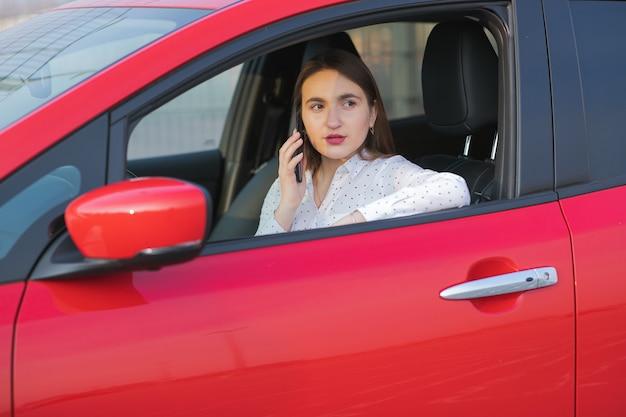 스마트 폰과 대기 전원 공급 장치를 사용하는 소녀는 자동차의 배터리를 충전하기 위해 전기 자동차에 연결됩니다. 전화로 얘기하는 긍정적 인 어린 소녀는 전기 자동차에 앉아서 충전.