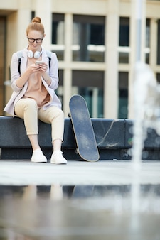 Девушка с помощью смартфона в городе