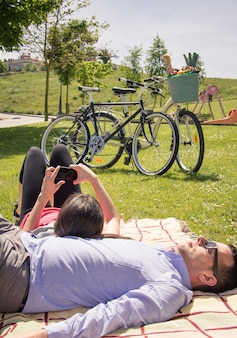 Girl using smartphone lying over man on the park