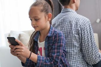Girl using smartphone near brother