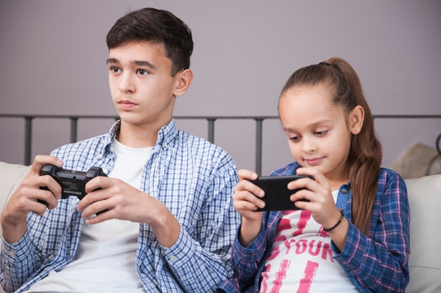 Girl using smartphone near teenager with controller