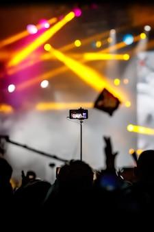 콘서트에서 비디오를 찍기 위해 삼각대에 스마트폰을 사용하는 소녀.