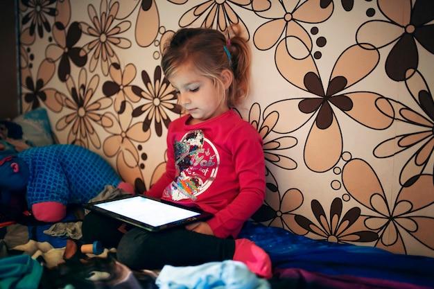 Девушка, использующая планшет возле стены