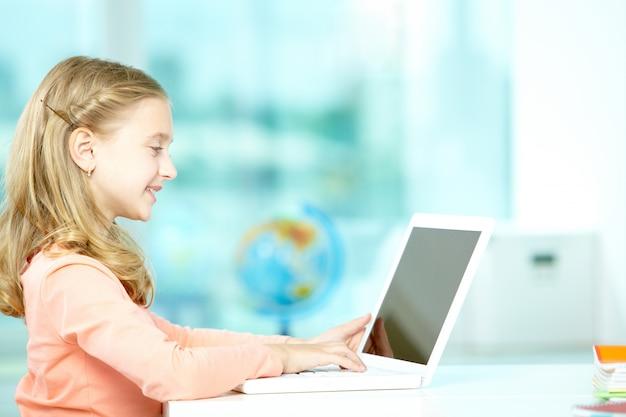 수업 시간에 노트북을 사용하는 소녀