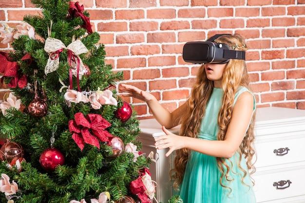 Девушка с помощью гарнитуры виртуальной реальности на новогодние праздники и наслаждайтесь.