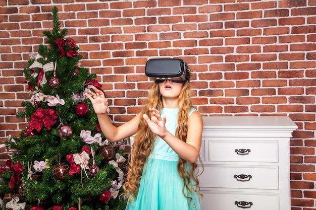 Девушка с помощью гарнитуры виртуальной реальности на новогодних праздниках