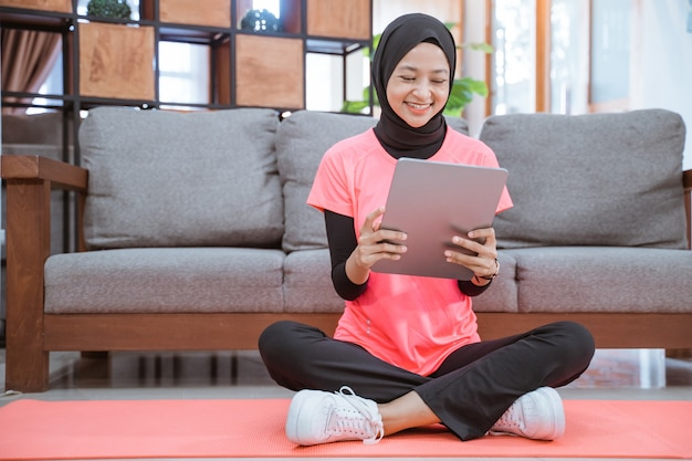 A girl in a veil gym outfit with a smile looking at a tablet after indoor exercise at home