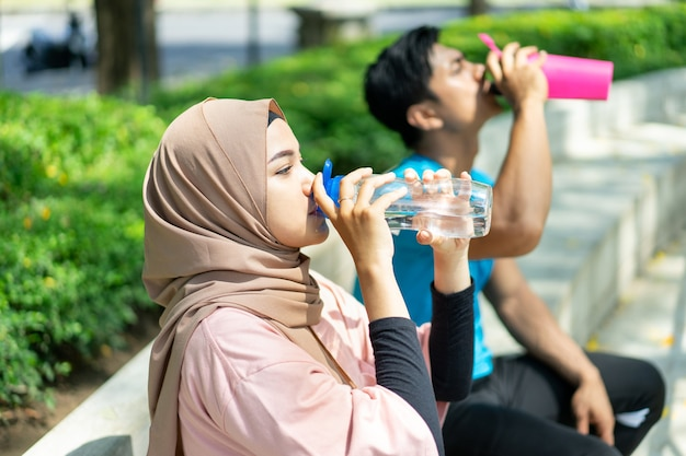 A girl in a veil and a young man sit drinking with a bottle after doing outdoor sports in the park