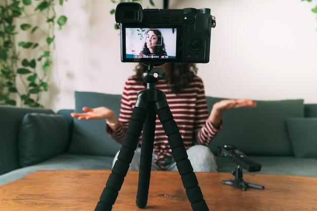 집에서 소녀 비디오 블로깅. 카메라에 선택적 초점입니다. 비디오 블로깅 개념