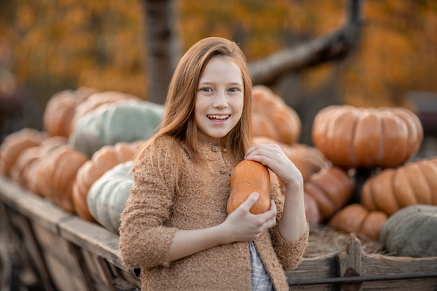A girl in a village on a farm holds a ripe pumpkin in her hands.