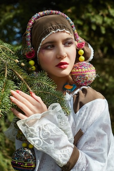 Girl in a vintage ethnic fashion handmade dress posing outdoors .