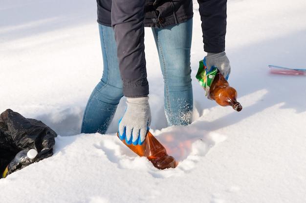 겨울에 쓰레기를 모으는 소녀 자원 봉사자
