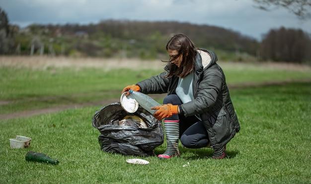 La ragazza volontaria raccoglie immondizia nella foresta, si prende cura dell'ambiente.