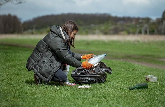 La ragazza volontaria raccoglie la spazzatura nella foresta, si prende cura dell'ambiente