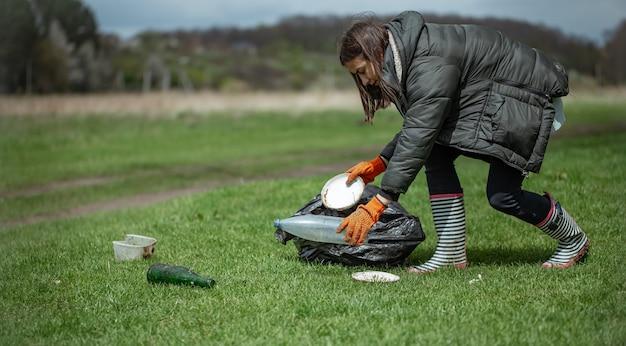 女の子のボランティアは、森のゴミを集め、環境を整えています。