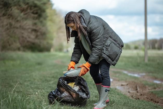 Девушка-волонтер собирает мусор в лесу, заботится об окружающей среде.
