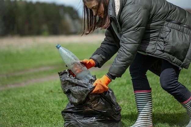 少女ボランティアが森でゴミを集め、環境に配慮しています。