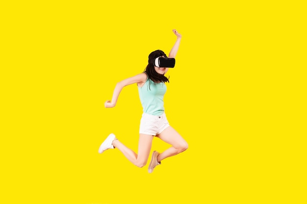 Girl in vr glasses of virtual reality is jumping on a yellow wall