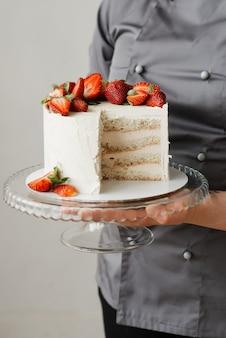 그녀의 손에 투명 트레이에 케이크 한 조각을 들고 소녀 웨이터
