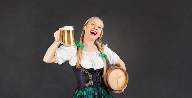 Девушка официантка октоберфест в национальном костюме с кружкой пива