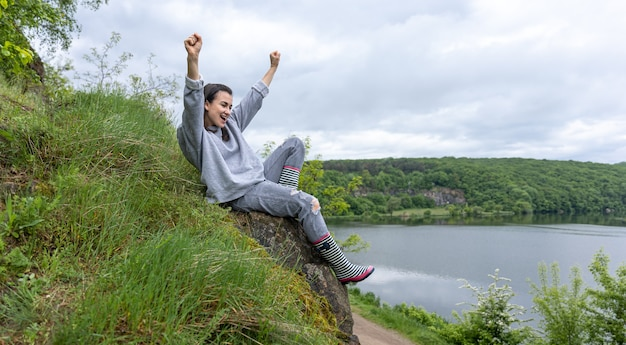 Una ragazza durante una passeggiata ha scalato una montagna in una zona montuosa e si rallegra.