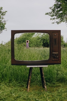 Girl walk in garden in old television frame outdoors, mental health