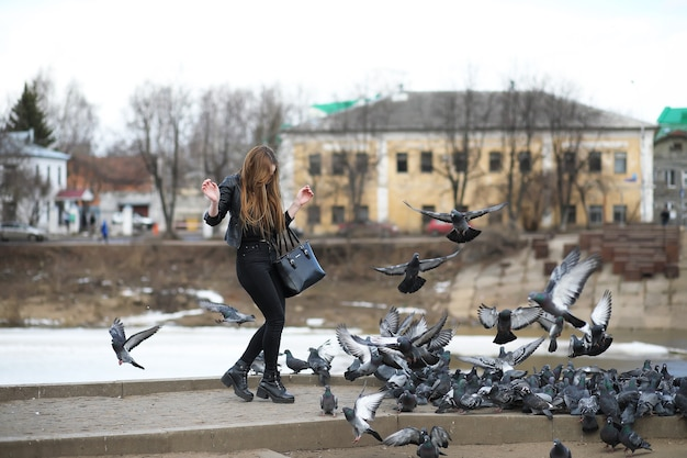 A girl on a walk in the park and a flock of pigeons