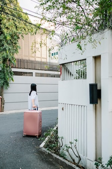 Girl walk with pink luggage