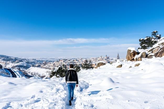 계곡에서 눈 덮인 통로 따라 걷는 소녀. 백그라운드에서 눈 덮인 도시 톨레도의 전망.