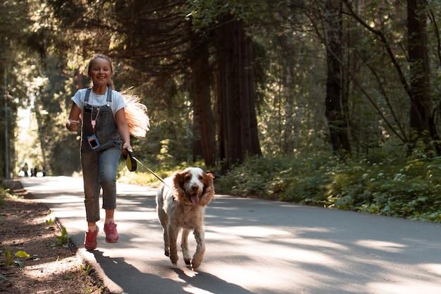 Девушка гуляет и бегает с собакой на гибком поводке в городском парке летом