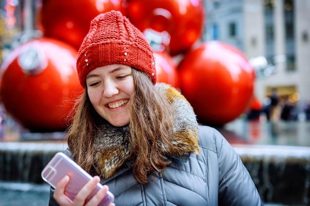 赤い帽子をかぶって通りでスマートフォンで歩いてテキストメッセージを送る女の子