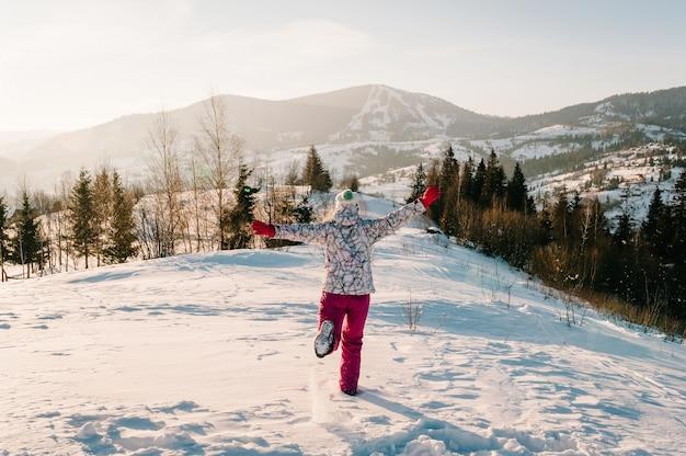歩いて戻って雪に覆われた冬の山々を見ている女の子。風景を楽しんでいます。自然の中を歩きます。霜の季節。寒い天気、丘の上の雪。ハイキング。晴れた冬の日の頂上に登山家。
