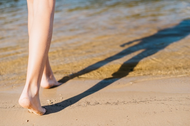 Girl walking barefoot on sand to coastline