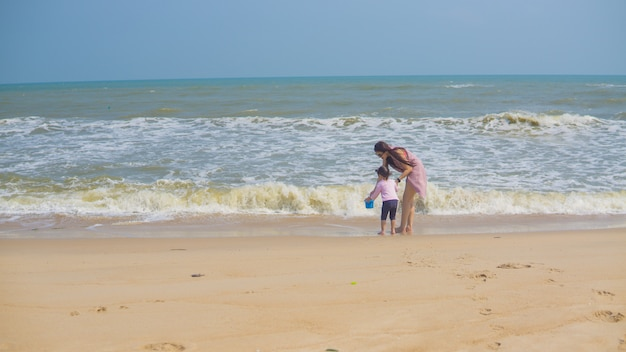 Girl walking to beach with mother holding hands