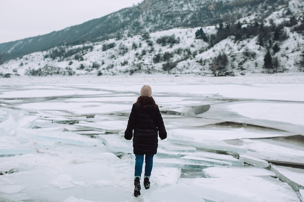 Girl walking on cracked ice of frozen river. winter day.