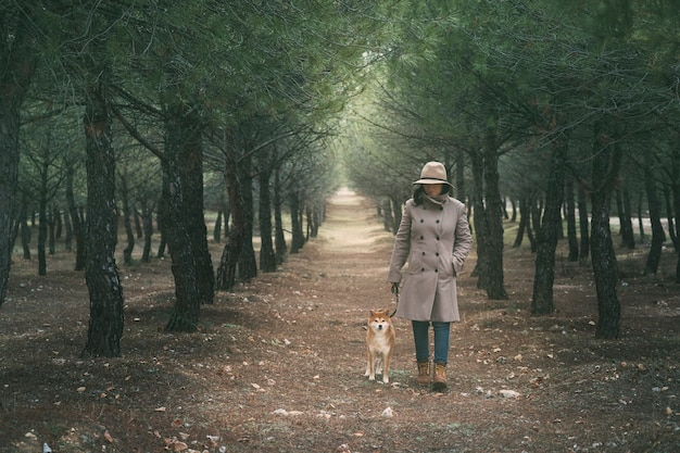 Girl walking her dog shiba inu through the field sheltered by the cold