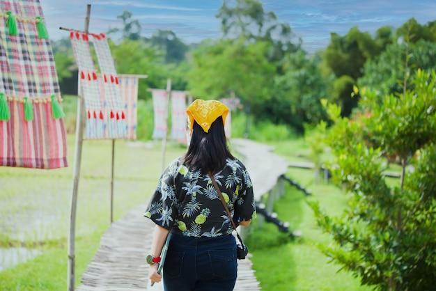 Девушка идет по деревянному мосту тропический мост подвесной мост пересечение реки