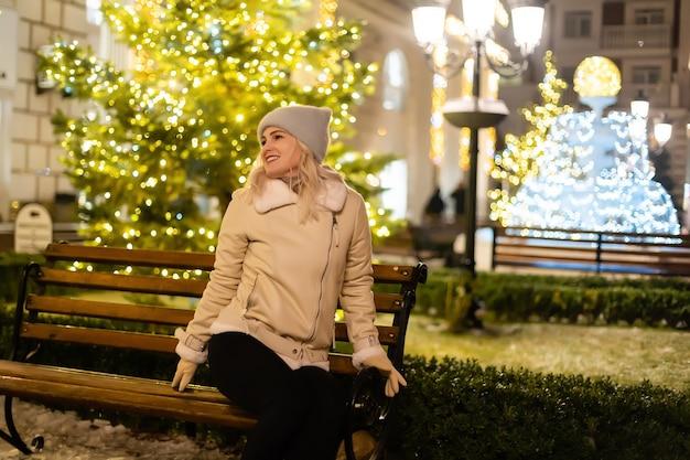 저녁에 크리스마스 조명으로 장식된 크리스마스 시장에서 걷는 소녀. 대도시에서 행복을 느낀다. 러시아 모스크바 붉은광장에서 겨울방학을 보내고 있다.