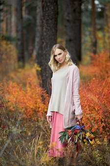 가 숲에서 산책 하는 소녀. 여자의 손에 있는 크고 아름다운 꽃다발. 소녀는 노란 붉은 잔디, 가을 자연에 서