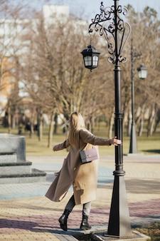 Девушка гуляет в городском парке в солнечный день