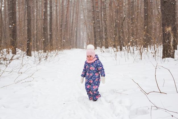 겨울 야외에서 걷고 눈을 던지는 소녀