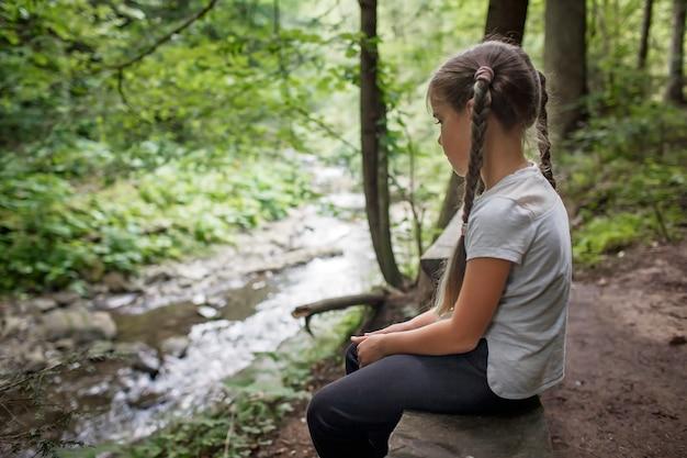 自然と自分自身の健康とゆっくりとした生活を探求するために森の中を一人で観光ハイキングをしている女の子