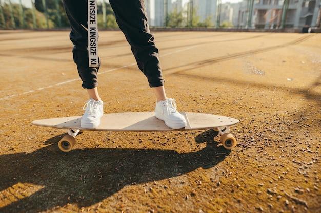 ロングボードの上を歩く女の子、足とボードのクローズアップ写真