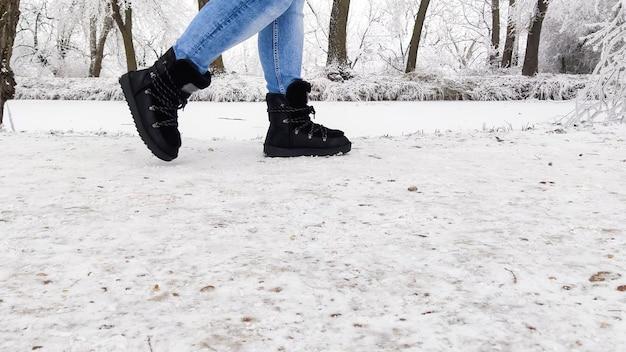 Девушка идет по снегу в черных сапогах в зимний полдень, с копией пространства.